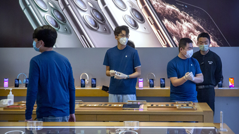Employees wear face masks as they stand in a reopened Apple Store in Beijing last week. Source: Associated Press